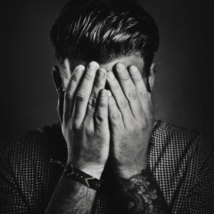 B/w portrait of a man hiding his face